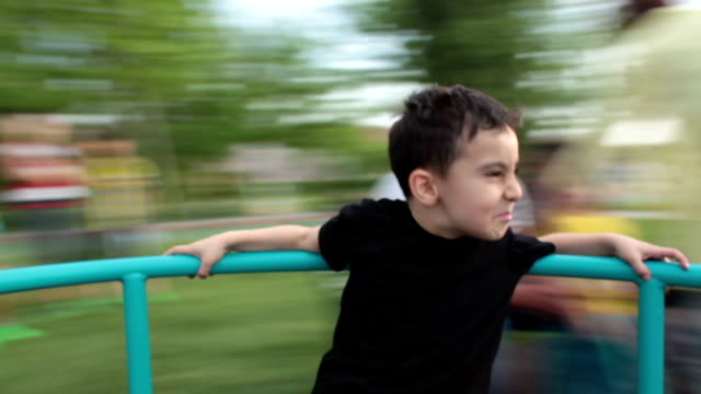 little boy spinning on playground - grimacing stock videos & royalty-free footage