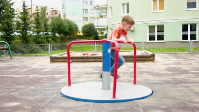 stockvideo's en b-roll-footage met jongetje spinnen op speelplaats - alleen jongens