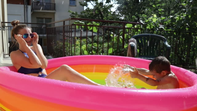little boy splashing water in his sister's face in inflatable pool - inflatable stock videos & royalty-free footage