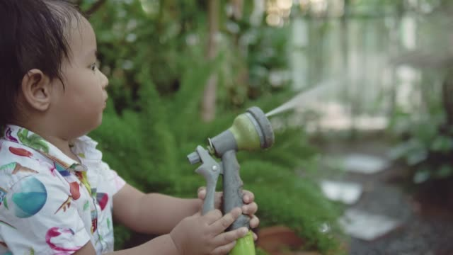 A little boy spraying water on plant at home.
