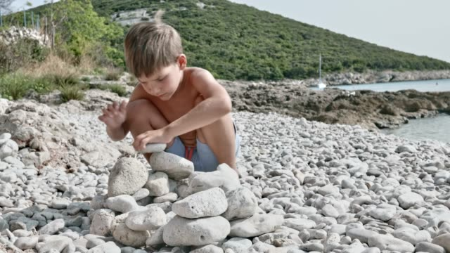 little boy stacking round white rocks on the beach in sunshine - crouching stock videos and b-roll footage