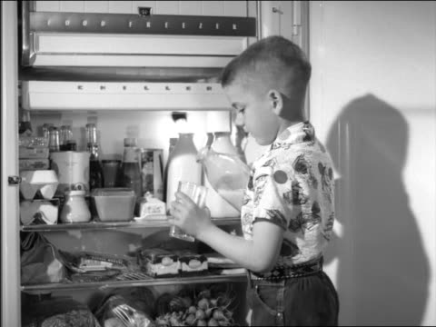 stockvideo's en b-roll-footage met b/w 1954 little boy standing in front of open refrigerator pouring + drinking milk - 1954