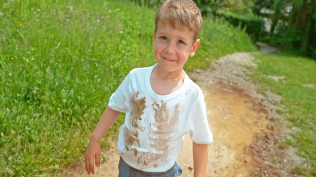 slo mo little boy standing in the puddle with a dirty white t shirt smiling into the camera - solo un bambino maschio video stock e b–roll