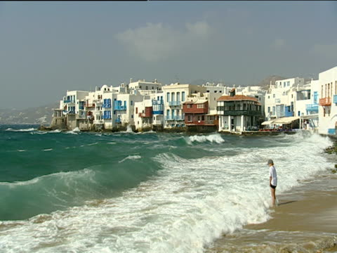 little boy stands on sea shore as big waves roll in and splash his legs whitewashed buildings in background - mykonos stock videos & royalty-free footage