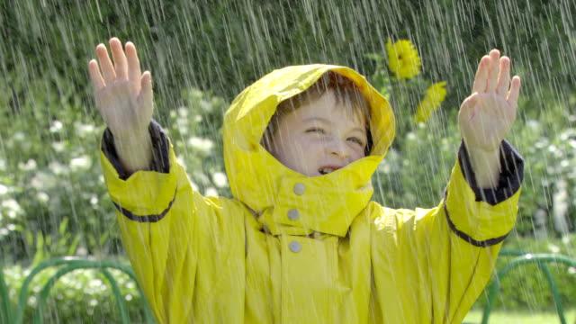 vídeos de stock, filmes e b-roll de a little boy stands out in the rain. - capa de chuva
