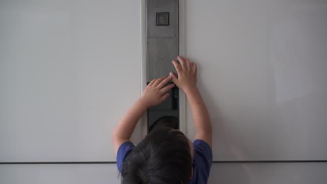 kleiner junge kämpft, um aufzug knopf zu erreichen - bemühung stock-videos und b-roll-filmmaterial