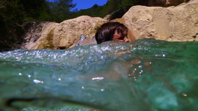 vídeos y material grabado en eventos de stock de little boy swimming on a river pool in the catalan pyrenees with clear water with underwater view in the catalan pyrenees. - bañador de hombre