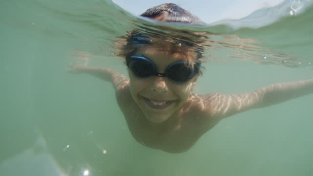 vídeos de stock e filmes b-roll de little boy swimming underwater in sea - 10 11 anos