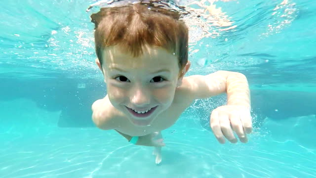 Little Boy Swimming Underwater in Swimming pool