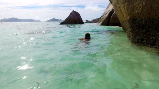 Little boy (7 years old) swims among the rocks of the beach Anse source d'argent - La Digue - Seychelles