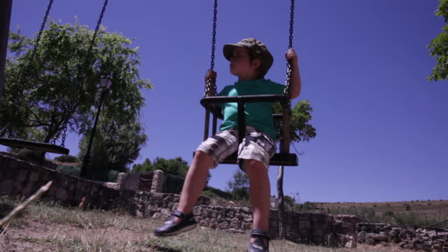 little boy swinging by himself. it´s day time and he is under the sun wear a hat for sun protection. - segovia stock videos & royalty-free footage