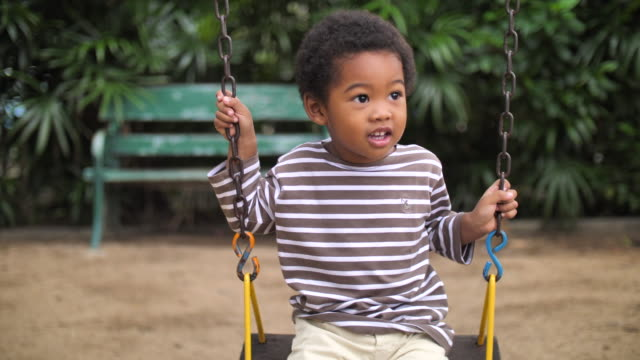 vídeos de stock, filmes e b-roll de garotinho balançando em um parque - balanço equipamento de playground
