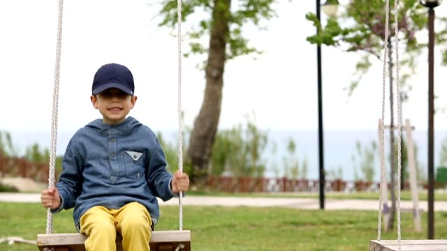 Little boy swinging  in park
