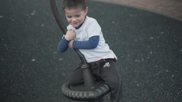 little boy swinging on playground equipment - rotorua stock videos and b-roll footage