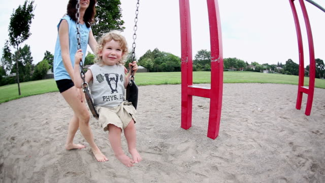 ms little boy swinging on swing and mother pushes little boy on swing / toronto, ontario, canada  - kelly mason videos stock videos & royalty-free footage