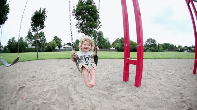MS Little boy swinging on swing at playground / Toronto, Ontario, Canada
