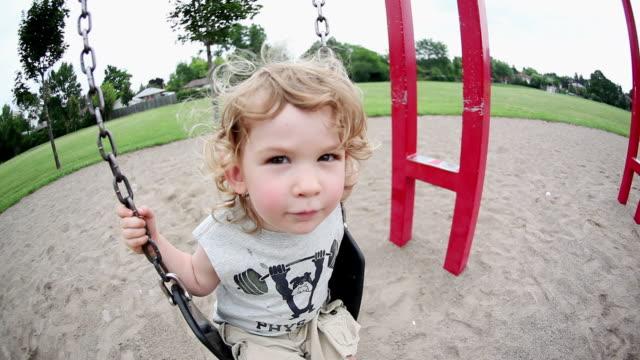 ms little boy swinging on swing at playground / toronto, ontario, canada  - kelly mason videos stock videos & royalty-free footage
