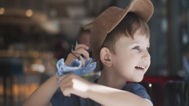 little boy taking off reusable protective fabric mask in a cafe - removing stock videos & royalty-free footage