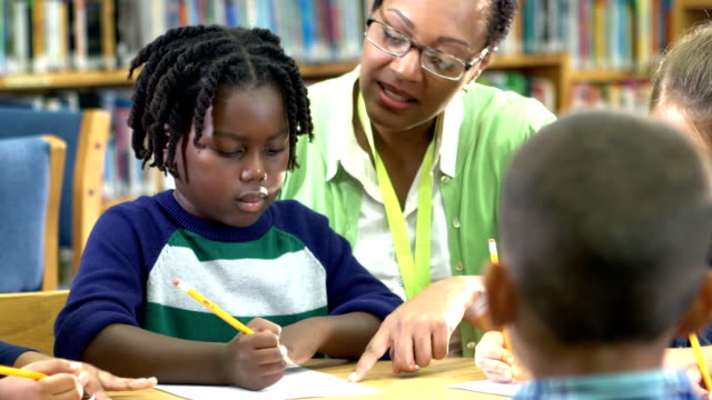 little boy, teacher, classmates writing in library - dreadlocks stock videos & royalty-free footage
