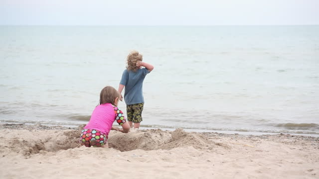 ms little boy throwing rock in water as little girl diging hole of sand on beach / toronto, ontario, canada - kelly mason videos stock videos & royalty-free footage