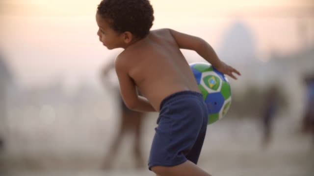 Little boy throws Brazilian flag soccer ball at the camera in slow motion on Copacabana Beach