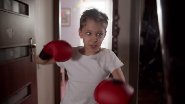 vidéos et rushes de petit garçon formant la boxe avec le sac de poinçonnage - petits garçons