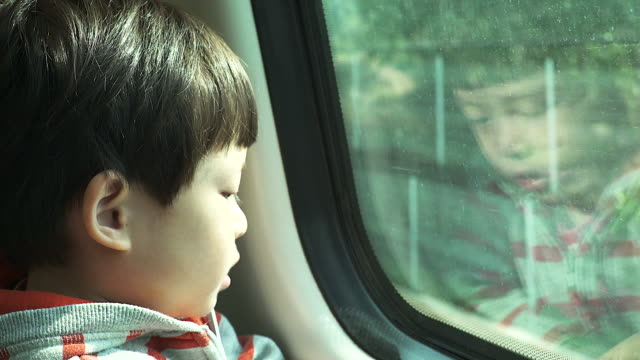 little boy traveling in train looking outside the window. - railroad car stock videos & royalty-free footage
