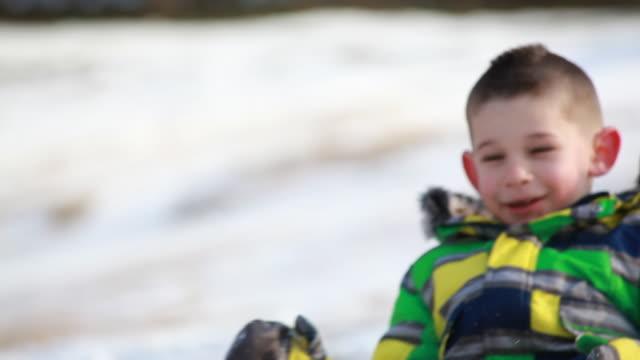vidéos et rushes de little boy travels down a snowy hill sitting on his snowboard towards camera - kelly mason videos