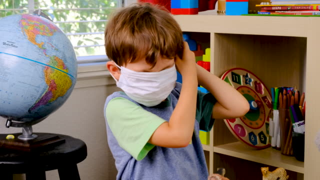 little boy trying to put in on a protective face mask - nursery school child stock videos & royalty-free footage