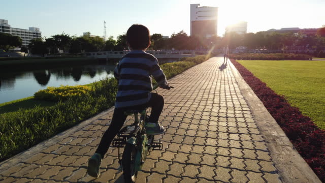 little boy trying to ride a bicycle - effort stock videos & royalty-free footage