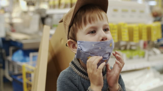 little boy trying to take off his protective mask in a shopping mall during pandemic - rimuovere video stock e b–roll