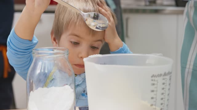 little boy using a spoon to put flour in a bowl - instrument of measurement stock videos & royalty-free footage