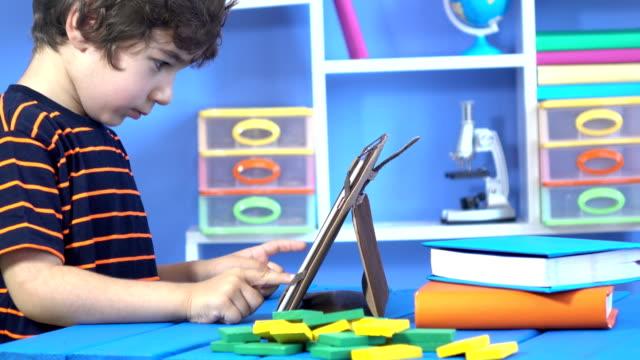 vídeos de stock, filmes e b-roll de garotinho, usando o tablet digital no quarto dele - old book