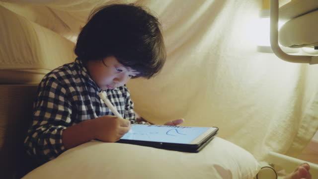stockvideo's en b-roll-footage met weinig jongen die digitale tablet in kleine tent thuis gebruikt - one baby boy only