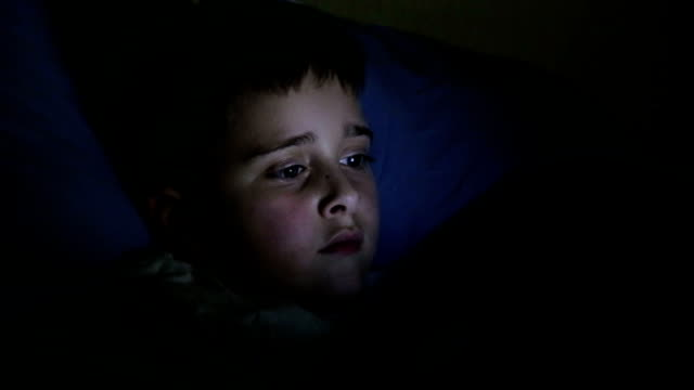 Little boy using tablet before sleep