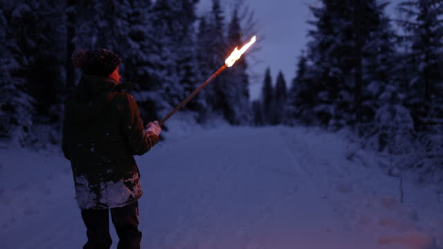 little boy walking alone with a flaming torch in winter forest at night - snow stock videos & royalty-free footage