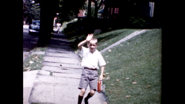 little boy walking out of his house holding a red lunch box on his way to his first day of school. - one boy only stock videos & royalty-free footage