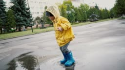 Little boy walking outdoors and jumping on puddle