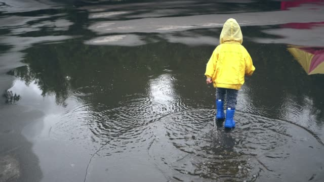 vídeos de stock e filmes b-roll de little boy walking outdoors and jumping on puddle - pequeno