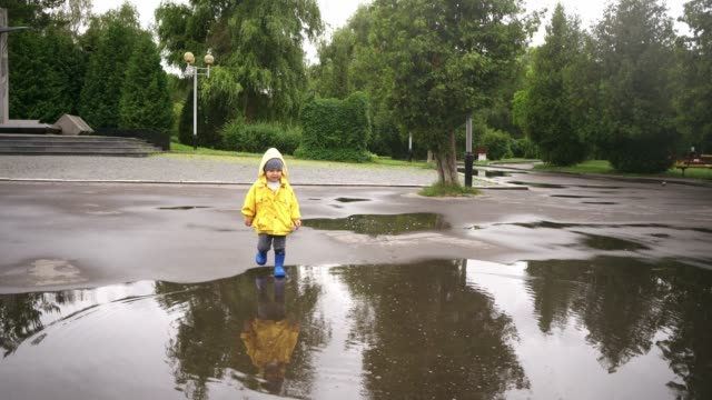 little boy walking outdoors and jumping on puddle - raincoat stock videos & royalty-free footage