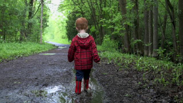 little boy walkling in water puddle on campground - ethnicity stock videos & royalty-free footage