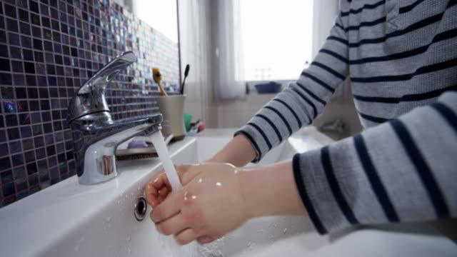 kleiner junge, der die hände gründlich wäscht - nur jungen stock-videos und b-roll-filmmaterial