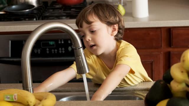 台所の流しで手を洗う小さな男の子 - キッチンシンク点の映像素材/bロール