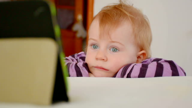 Little boy watching cartoon on the tablet with interest
