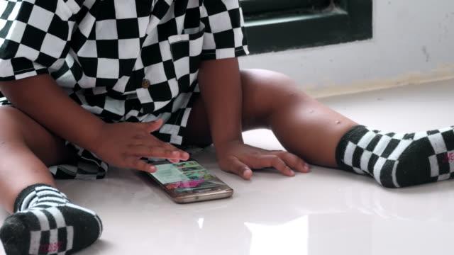 kleiner junge beobachtet auf tablet-smartphone - männliches baby stock-videos und b-roll-filmmaterial