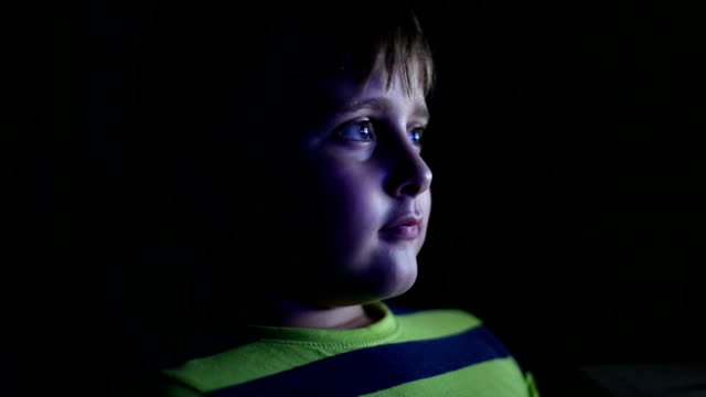 Little boy watching TV at night