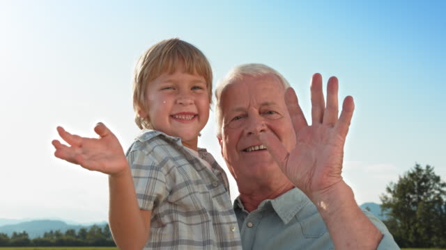 SLO MO Little boy waving into the camera while being held by his grandfather