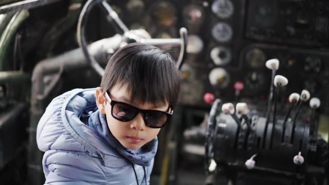 a little boy wearing a pair of sunglasses in the cockpit of old airplane - one baby boy only stock videos & royalty-free footage