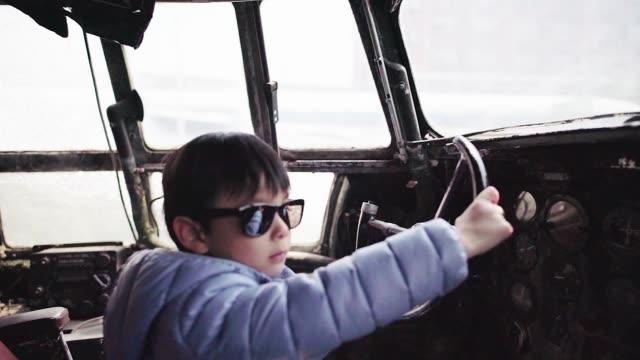 a little boy wearing a pair of sunglasses in the cockpit of old airplane - mar bildbanksvideor och videomaterial från bakom kulisserna