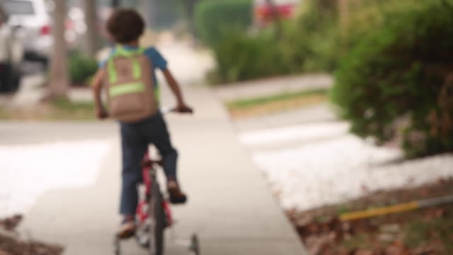 little boy wearing a protective face mask going back to school riding his bicycle carrying a backpack - schoolboy stock videos & royalty-free footage